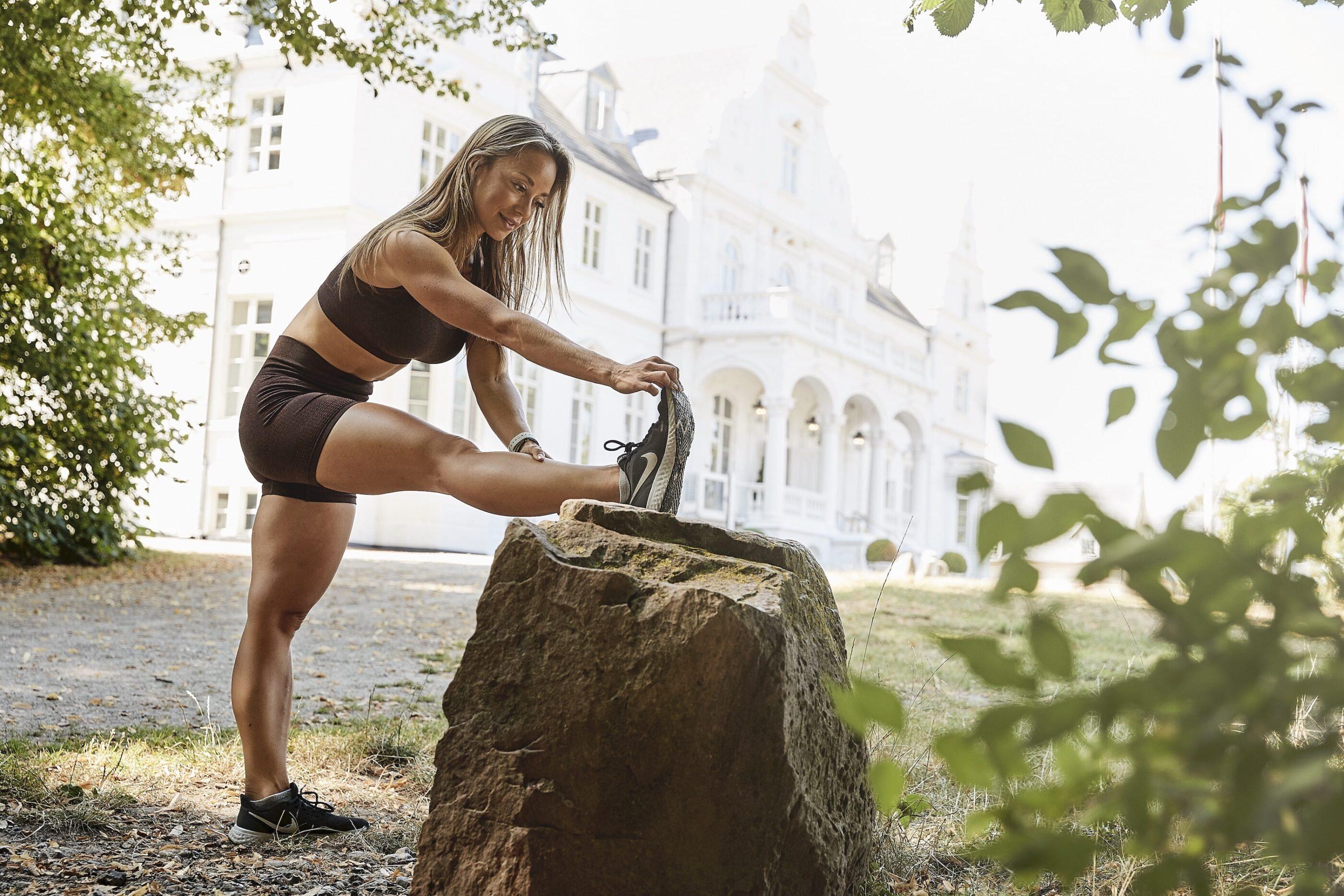 En kvinde strækker ud ved en stor sten ved hotellets gård