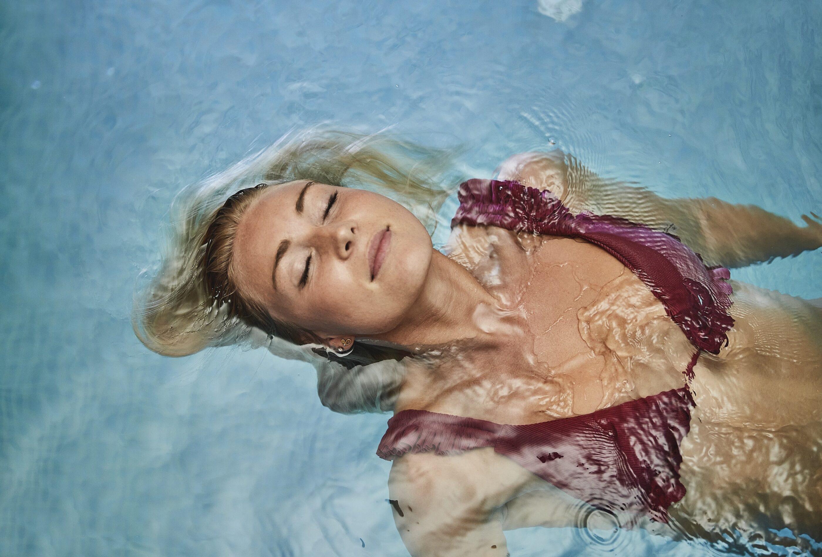 En kvinde ligger og bader rygcrawl i svømmepoolen med øjnene lukkede