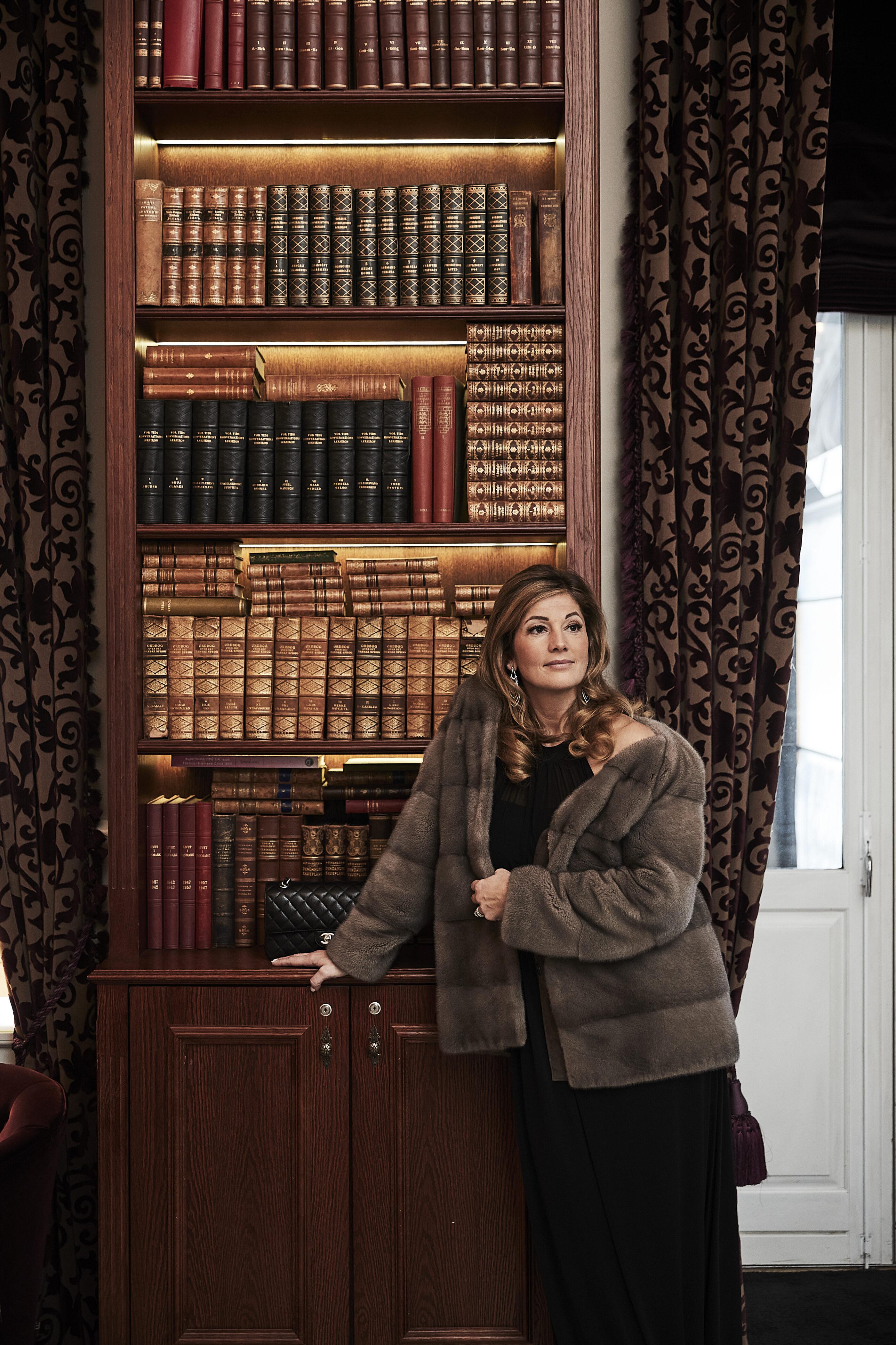 Kvinde står foran bogreol i pelsjakke på kokkeda slot