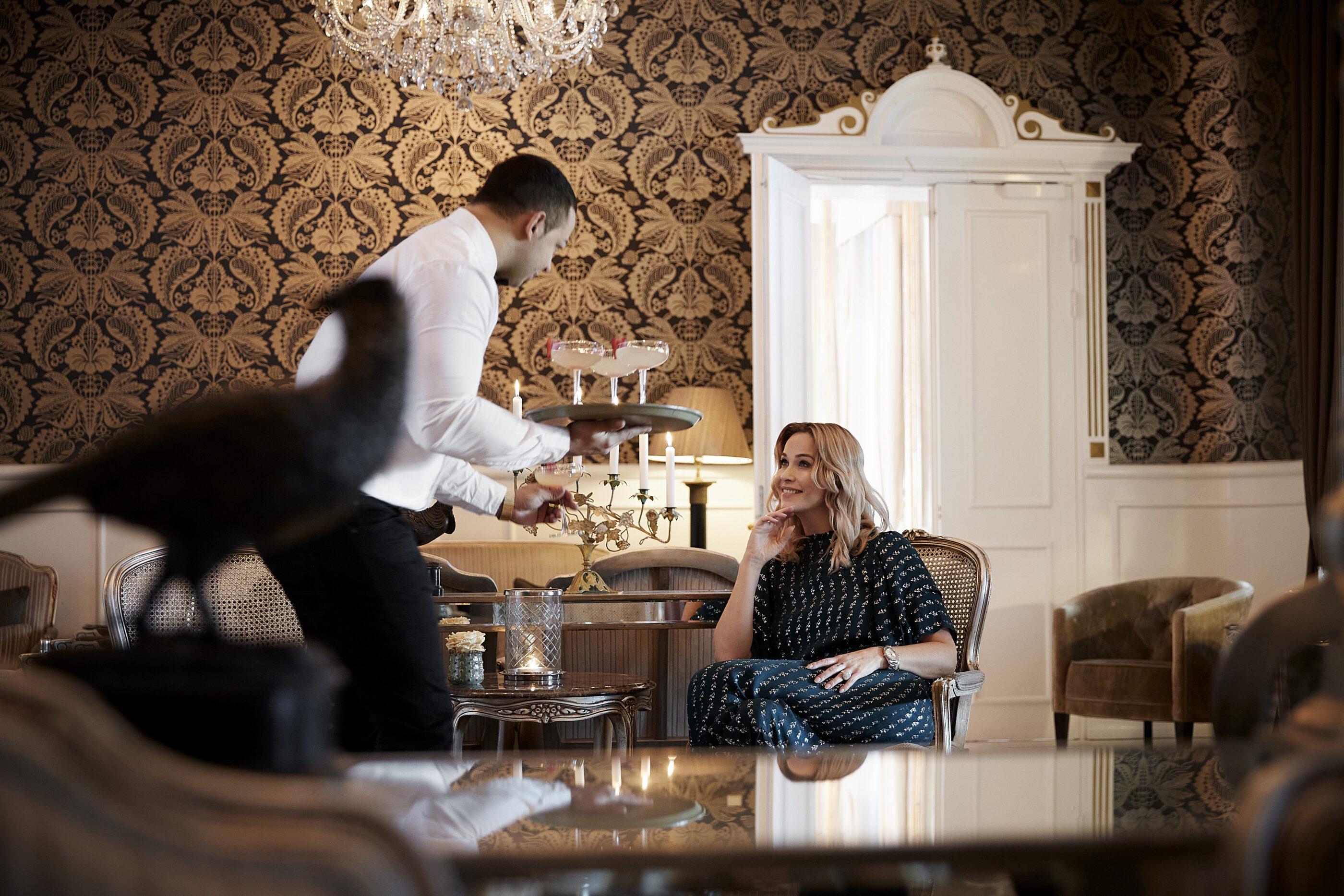 Tjener serverer cocktail i loungen til en kvinde
