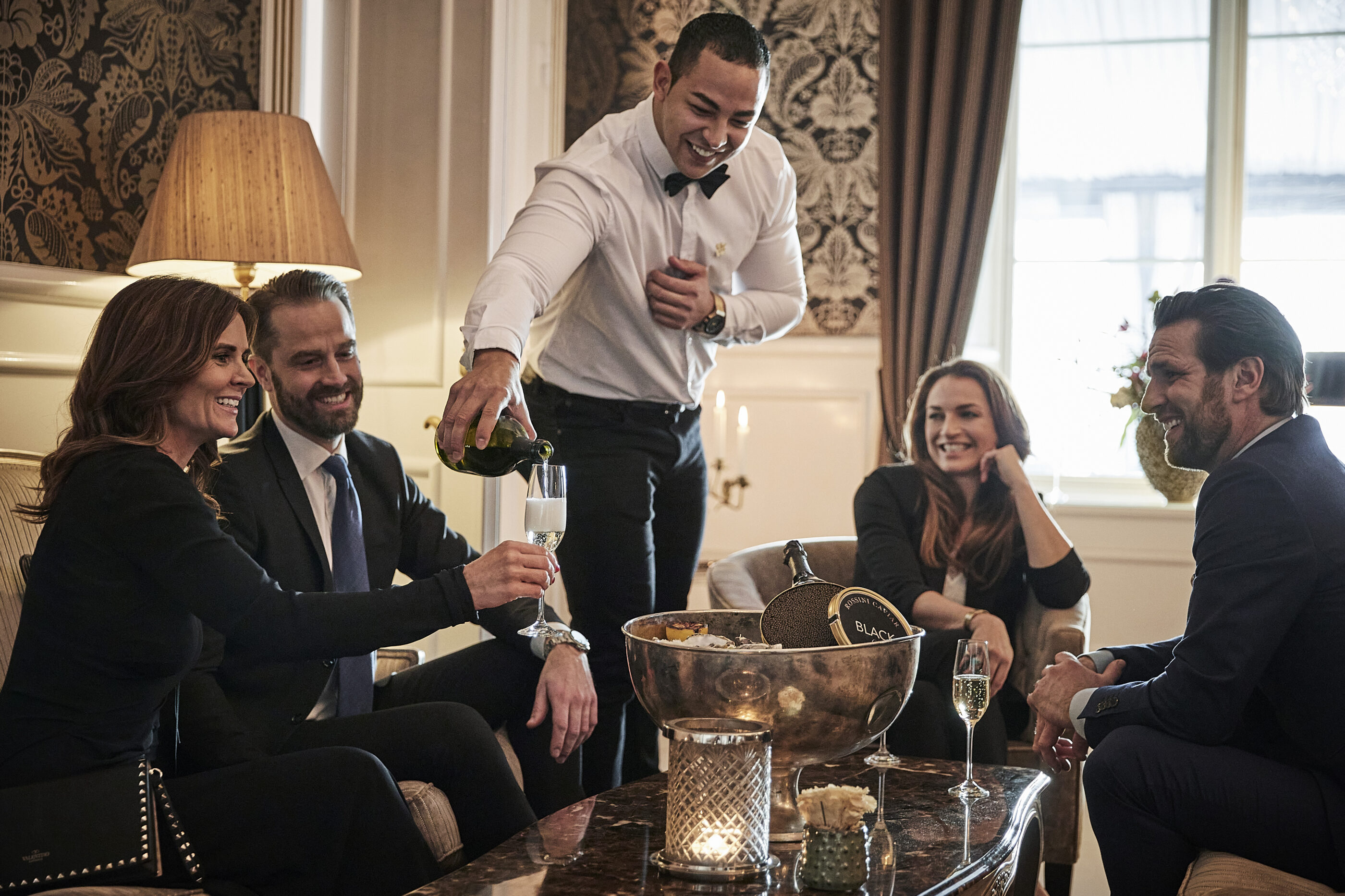 Waiter pouring champagne into glasses for guests