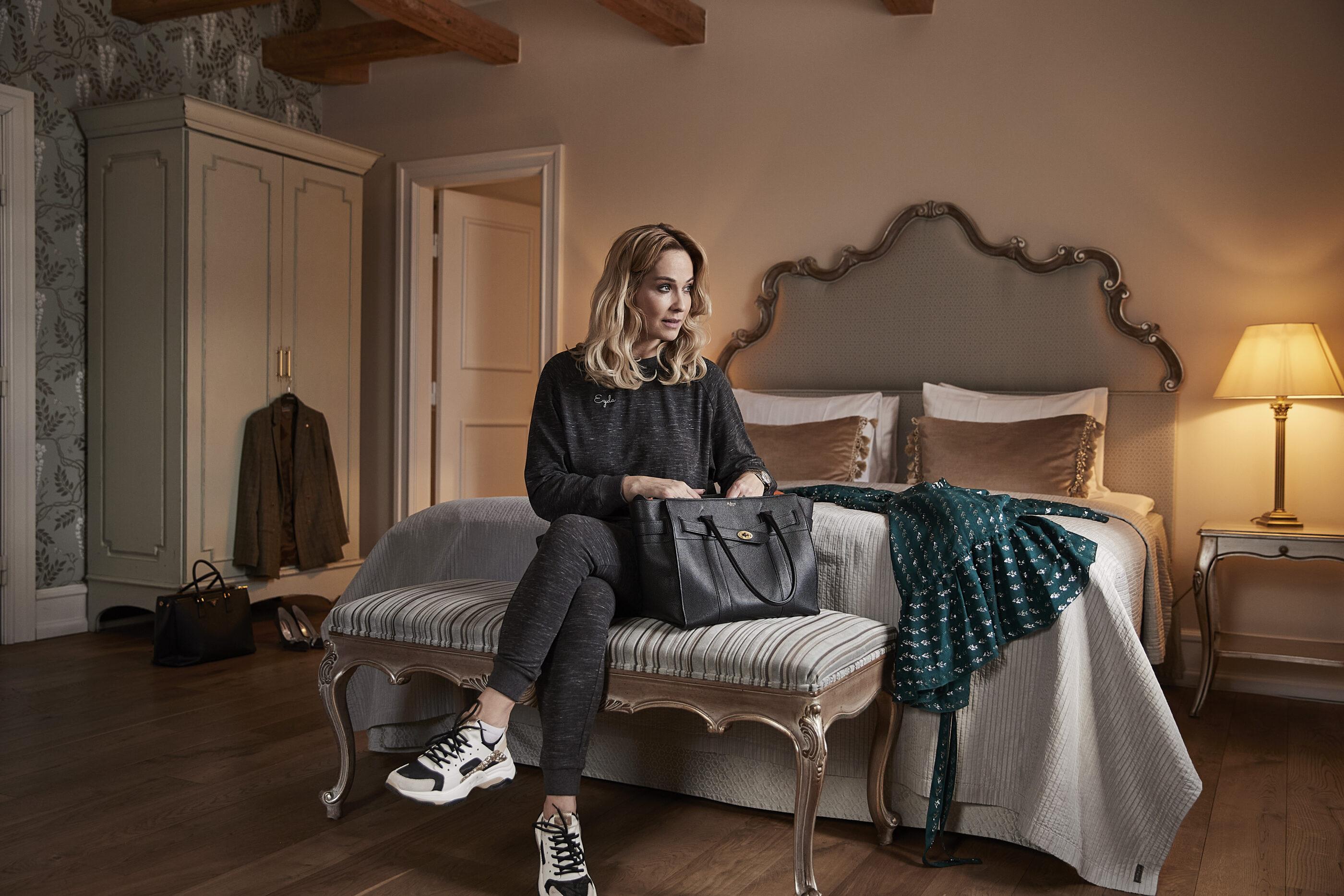 En kvinde sidder ved sengen på værelset