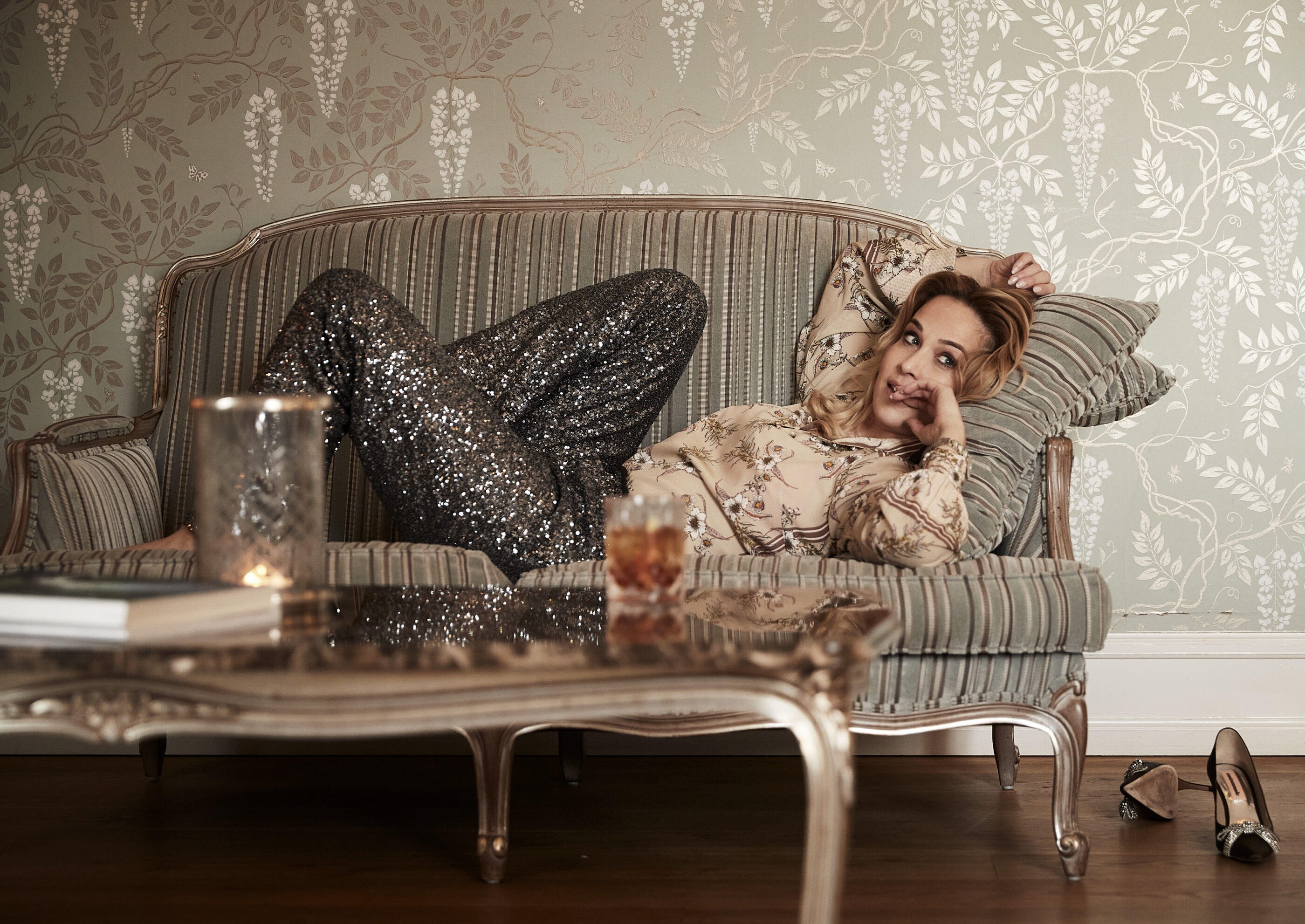 Kvinde flyder på sofaen i værelset med en drink