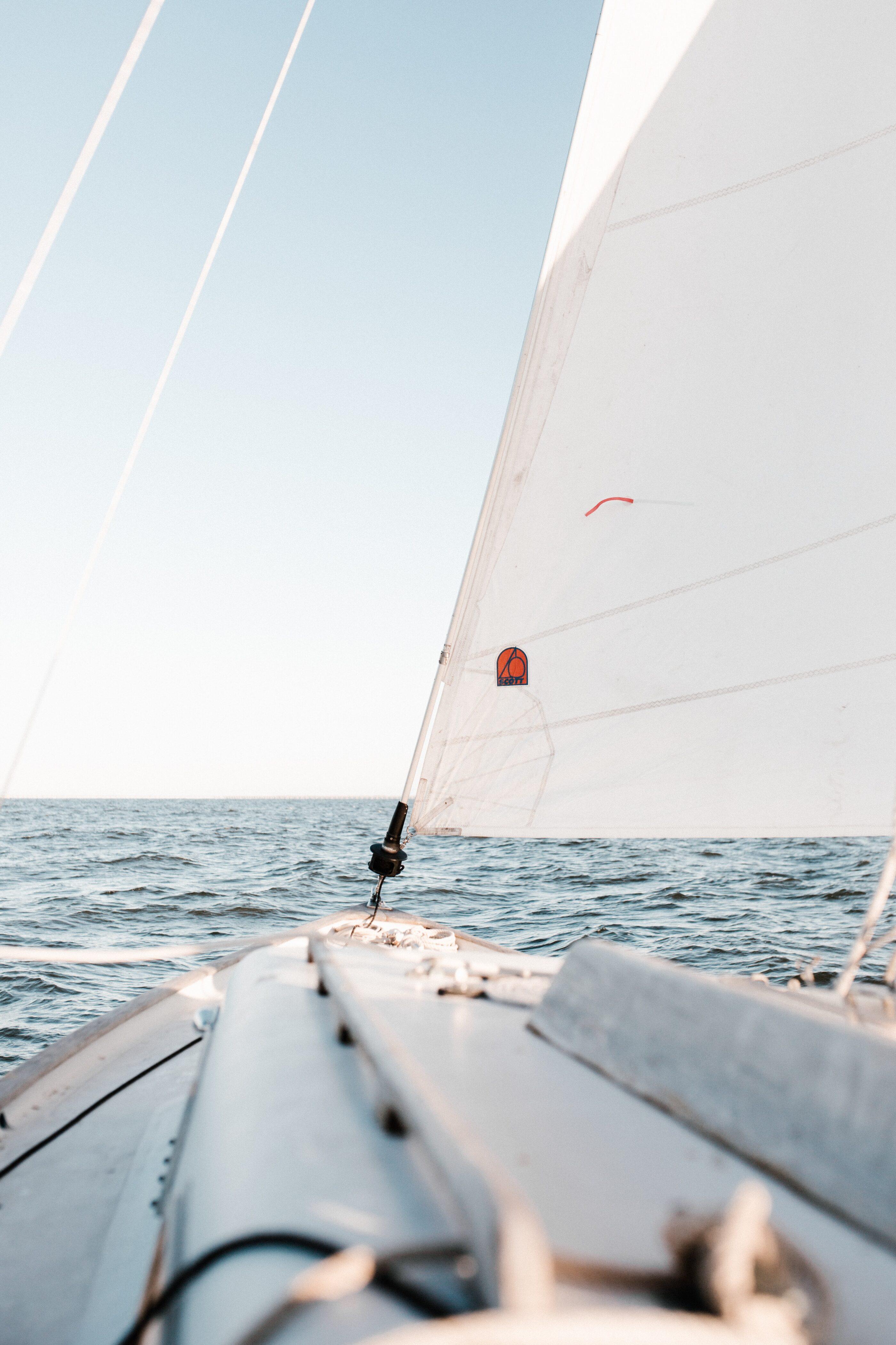En hvid sejlbåd ude i havet under klar himmel