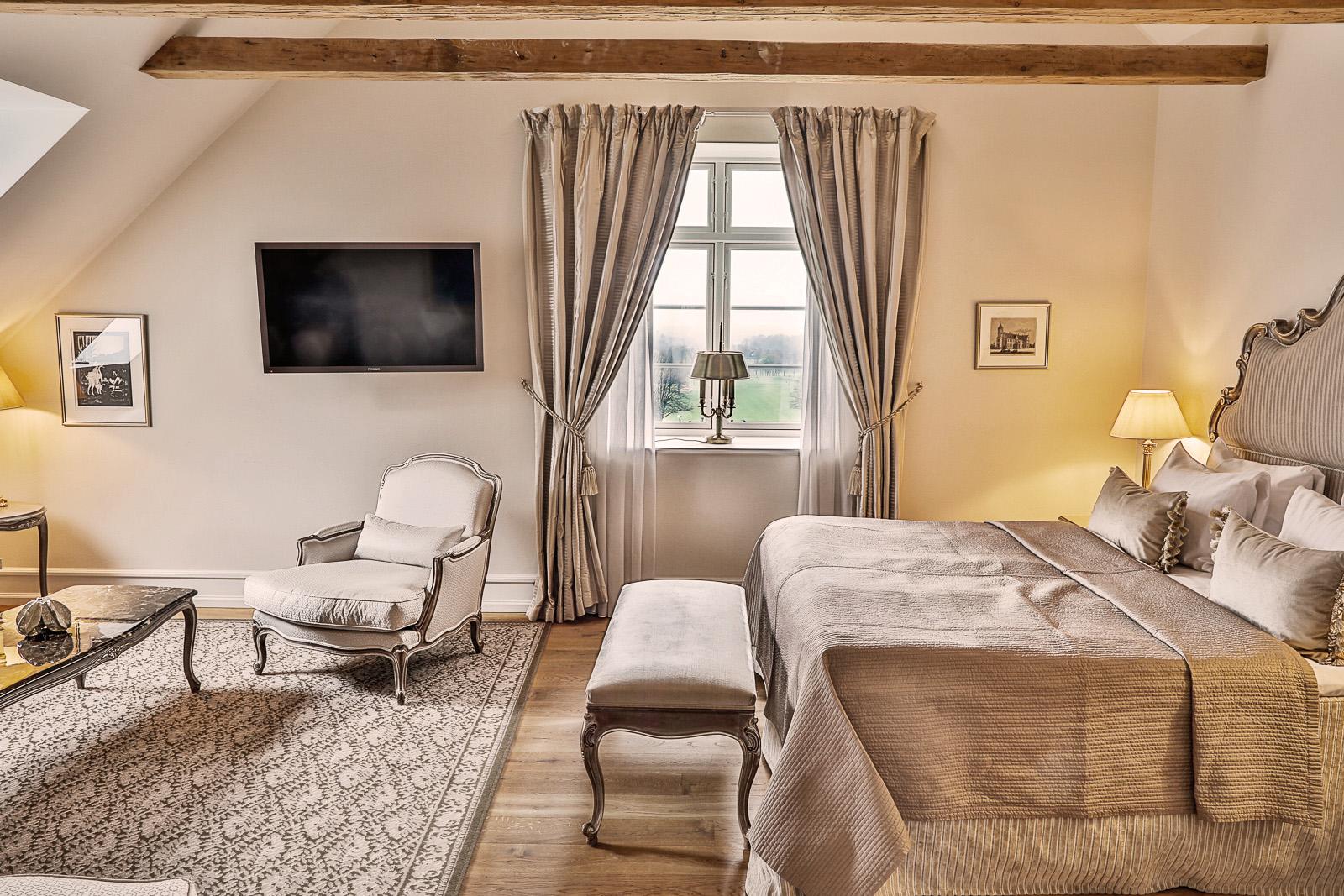 Luksus soveværelse med sølv-grå farvet sengetøj og gardiner.